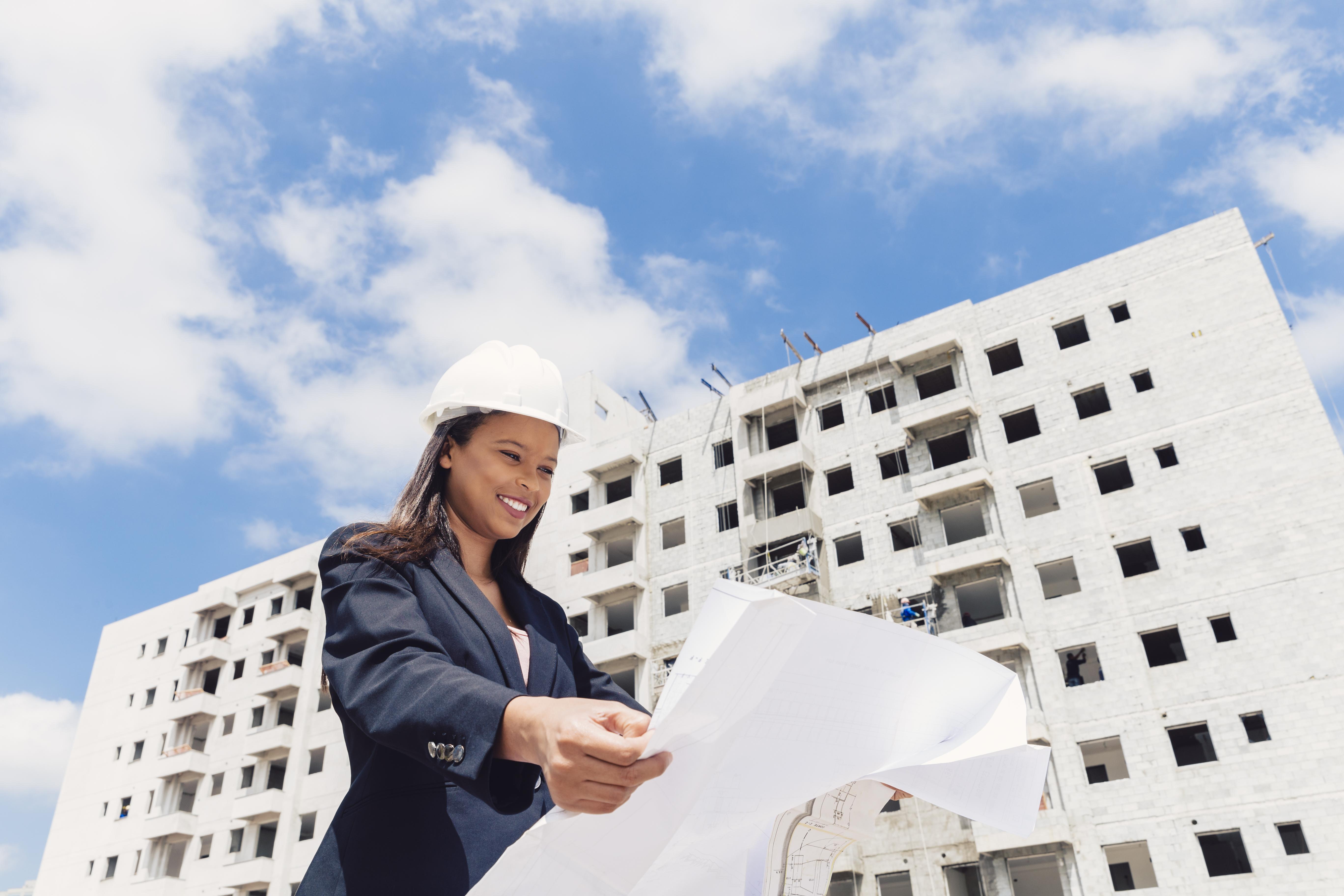 femme avec un casque devant un immeuble