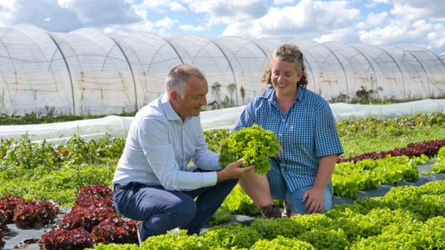 David Sagot dans un champ de salades avec l'agricultrice